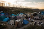 CALAIS, FRANCE - AUGUST 02: The sun sets behind a make shift camp near the port of Calais on August 2, 2015 in Calais, France. Hundreds of migrants are continuing to attempt to enter the Channel Tunnel and onto trains heading to the United Kingdom. (Photo by Rob Stothard/Getty Images)